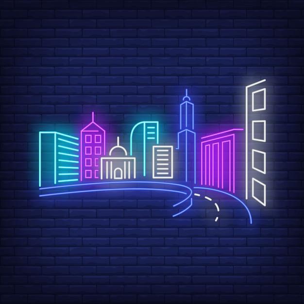 都市の建物と道路のネオンサイン。 無料ベクター