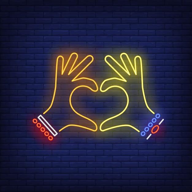 Руки женщины показывая жест сердца неоновую вывеску Бесплатные векторы