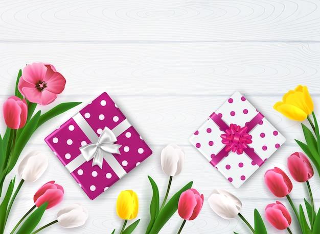 Композиция ко дню матери с подарочными коробками и цветами в горошек на деревянном фоне Бесплатные векторы