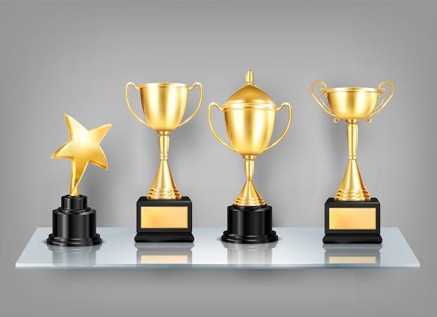Трофей награждает реалистичными изображениями на полке композицию из золотых кубков с черными постаментами на стеклянной полке Бесплатные векторы