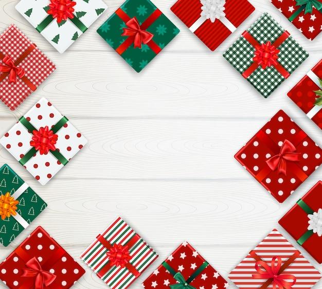 Реалистичный фон с рисунком украшенные рождественские коробки на белом деревянном столе Бесплатные векторы