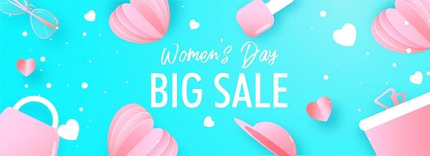 ピンクの紙で大きな販売ヘッダーまたはバナーデザインカットハート、ギフトボックス、ゴーグル、ハンドバッグ、女性の日の青色の背景に飾られたマニキュア。 Premiumベクター
