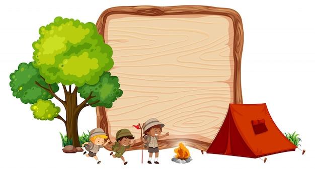 木製のバナーでのキャンプの子供たち Premiumベクター