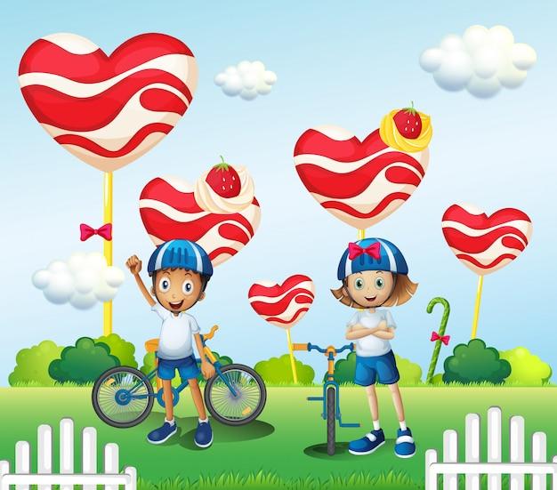 男の子と女の子が巨大なキャンディーの近くでサイクリング 無料ベクター