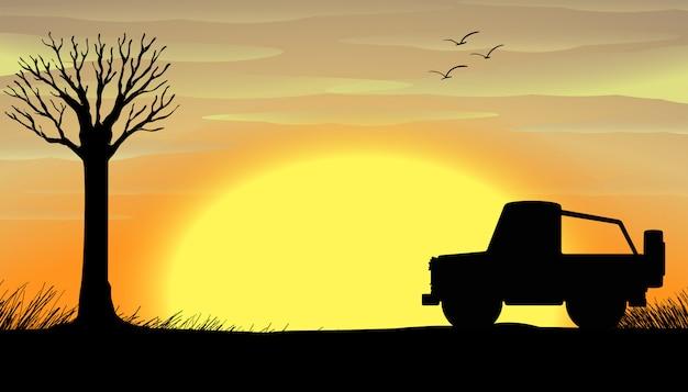 トラックとシルエットの夕日のシーン 無料ベクター