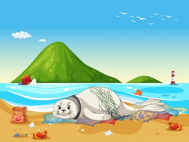 ビーチでシールとプラスチックのゴミのシーン Premiumベクター