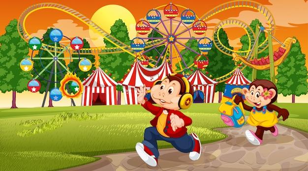 猿の子供と遊園地のシーン 無料ベクター