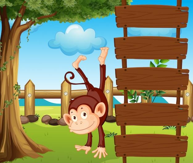 空の木製看板の横にある類人猿 無料ベクター