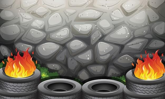 Горящие шины возле каменной стены Бесплатные векторы