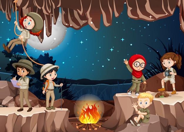 Сцена с группой разведчиков, исследующих пещеру Бесплатные векторы