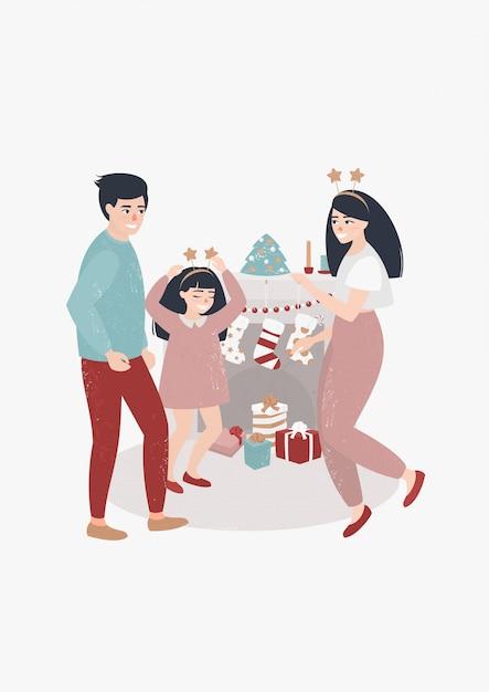 クリスマスの日に暖炉のそばで踊る家族 Premiumベクター