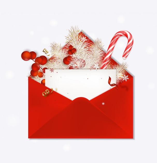Открыт красный конверт с рождественской поздравительной открыткой. конфета, еловые ветки, красные ягоды, праздничное оформление Premium векторы