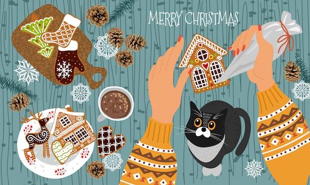 -ペストリーバッグを持つ手は、プロセスを見てアイシングと猫とジンジャーブレッドクッキーを飾る Premiumベクター