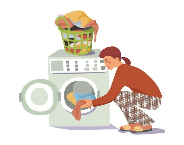 Молодая женщина загружает грязное белье в стиральную машину Premium векторы