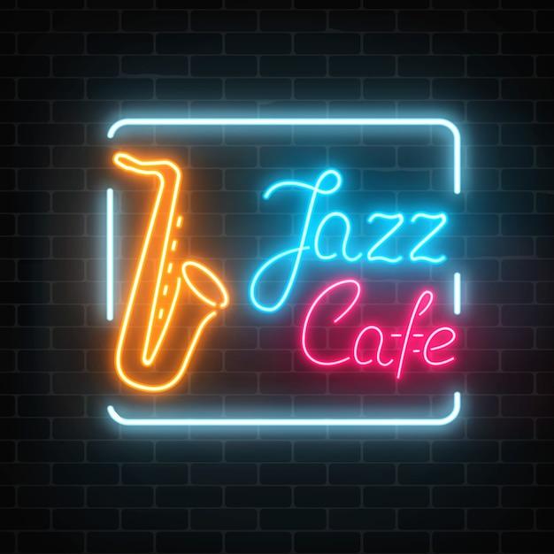 暗いレンガの壁にネオンジャズカフェとサックスの輝くサイン。 Premiumベクター