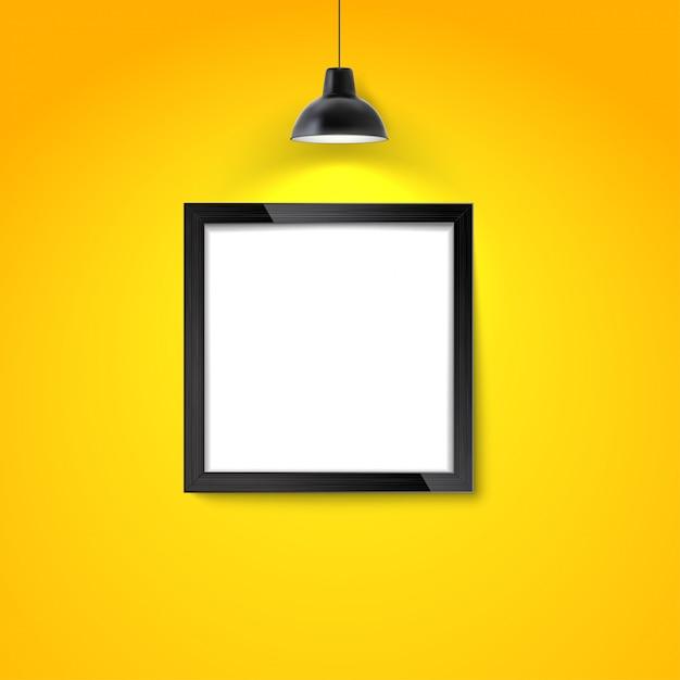 掛かるランプが付いている黄色の壁の額縁。空白のフォトフレームまたはポスターテンプレート。 Premiumベクター