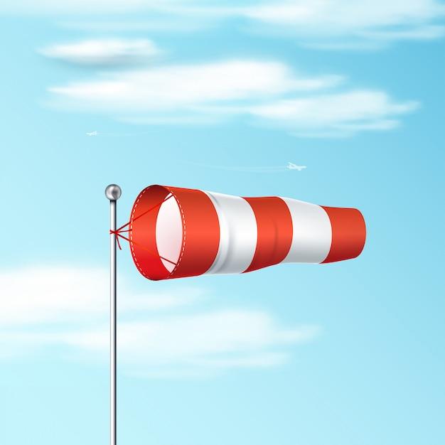青い空に吹流し。風向と風速を示す赤と白の空港風旗。リアルなイラスト。 Premiumベクター