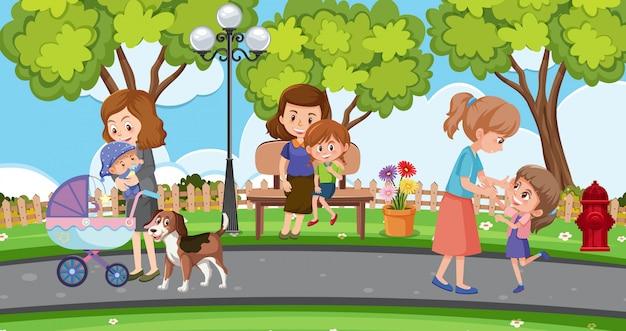 公園でくつろぐ母親と子供たちとのシーン Premiumベクター