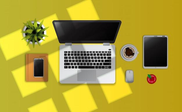 ノートパソコン、ガジェット、ノートブック、ウィンドウの日光と黄色の机の上のカップコーヒートップビュー Premiumベクター