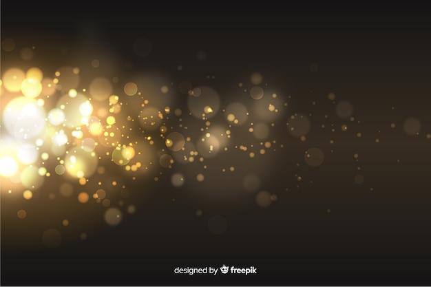 金色の粒子の背景のボケ味 無料ベクター