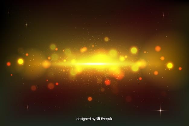 金色の粒子と背景のボケ味 無料ベクター