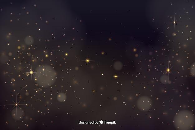 黄金の粒子と背景のボケ味 無料ベクター