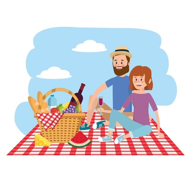 自然の女性と男はテーブルクロスのバスケットとカップル Premiumベクター