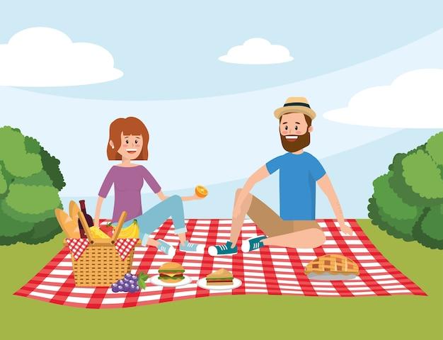楽しい女性と男カップルのテーブルクロスでバスケット Premiumベクター