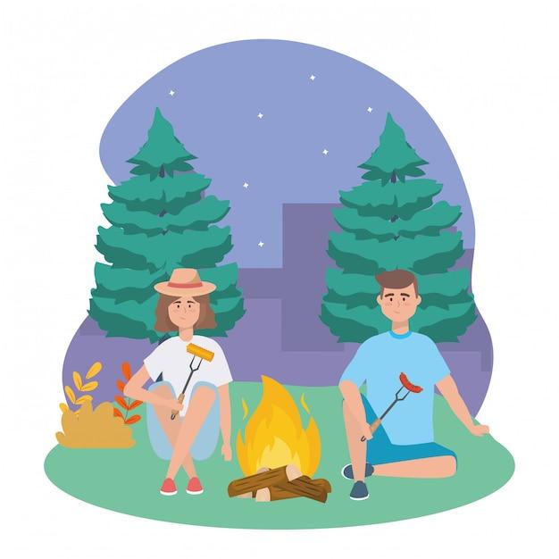 男と女の薪の火とソーセージの穂軸 無料ベクター