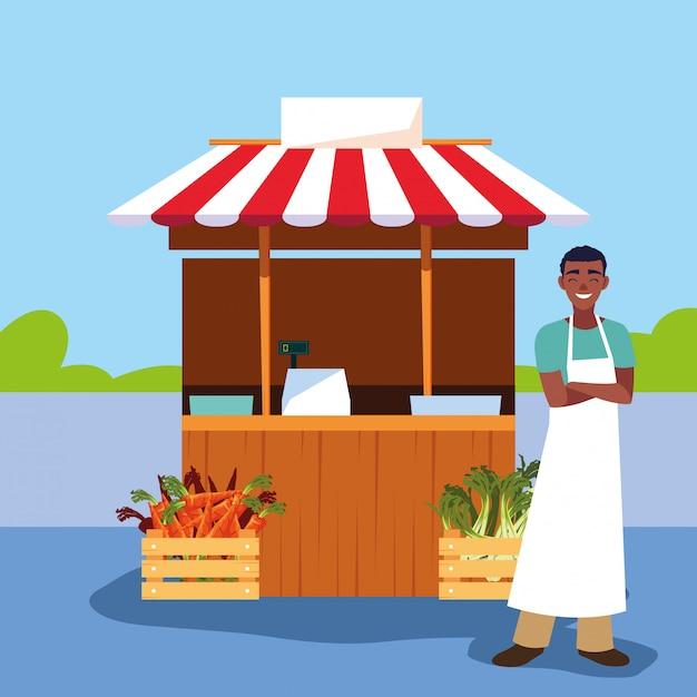 店の野菜の屋台キオスクを持つセールスマン Premiumベクター