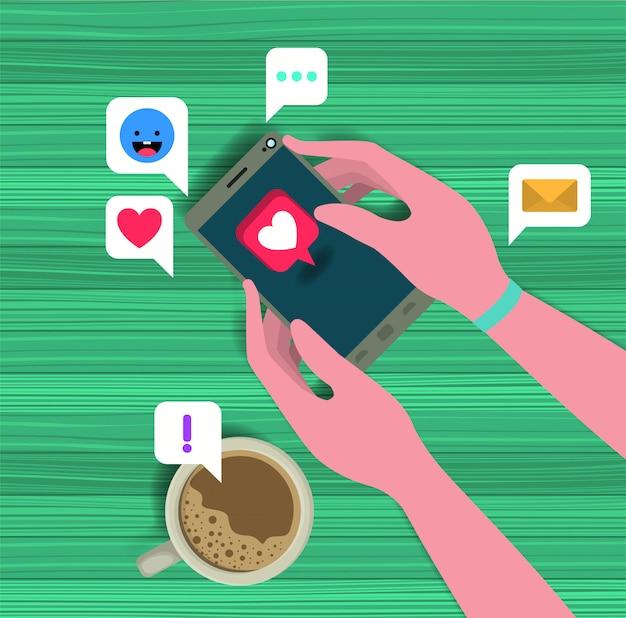 コーヒーカップとソーシャルアイコン付きスマートフォンを使用して手 Premiumベクター