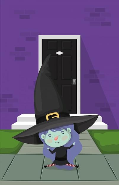 Маленькая девочка с костюмом ведьмы в дверях дома Premium векторы