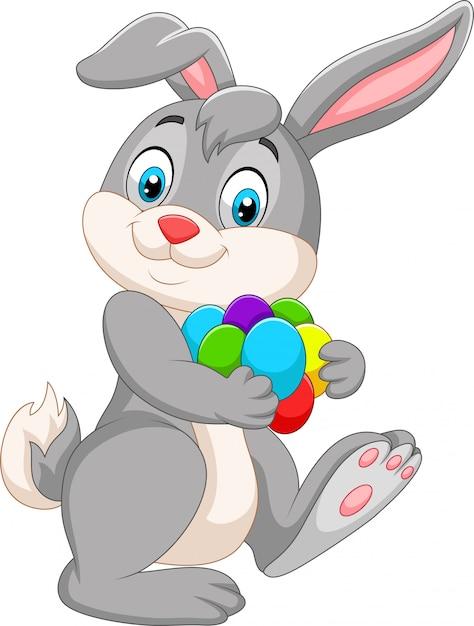 Мультяшный пасхальный кролик с разноцветными яйцами Premium векторы