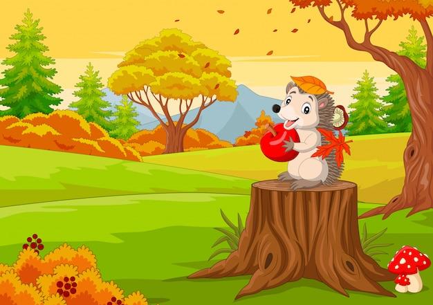Мультяшный ежик держит красное яблоко в осеннем лесу ...