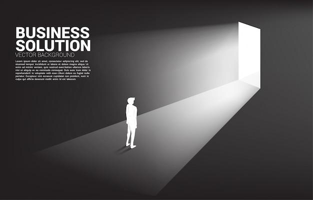 出口のドアの前に立っている実業家のシルエット。キャリアアップのコンセプトとビジネスソリューション。 Premiumベクター