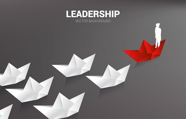 白をリードする赤い折り紙の紙の船のビジネスマンのシルエット。 Premiumベクター