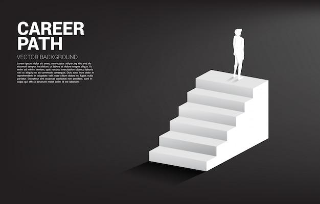 階段の上に立っている実業家のシルエット Premiumベクター