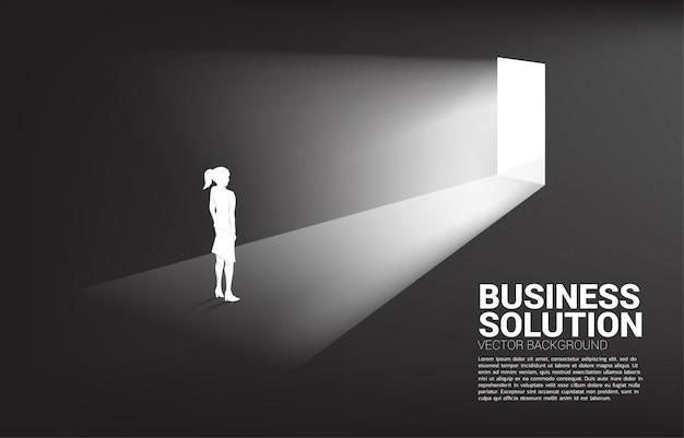 Силуэт бизнесвумен, стоя перед фоном выходной двери Premium векторы