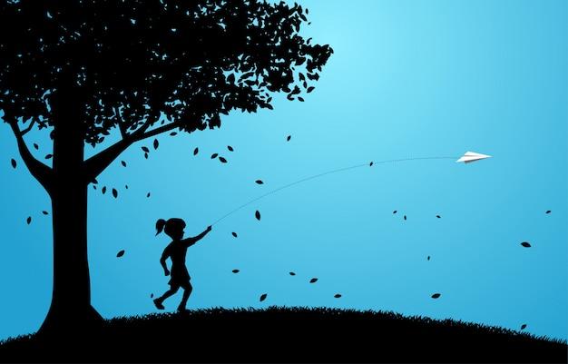 Силуэт девушки работает, чтобы выбросить оригами бумажный самолетик под большим деревом. Premium векторы