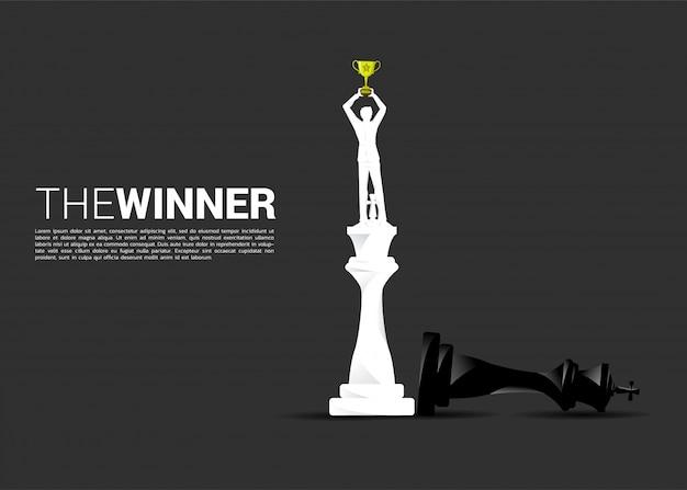 チェックメイトに勝者チェスの上に立って実業家のシルエット。 Premiumベクター