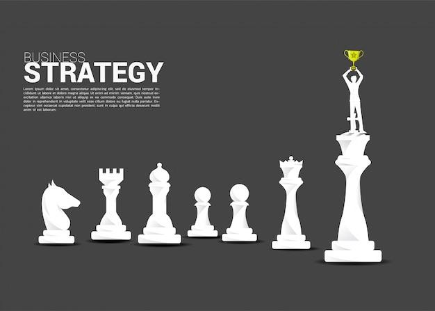 キングチェスの駒の上に立って実業家のシルエット Premiumベクター