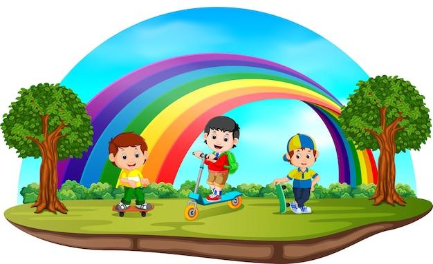 虹の日に公園で遊んでいる子供たち Premiumベクター