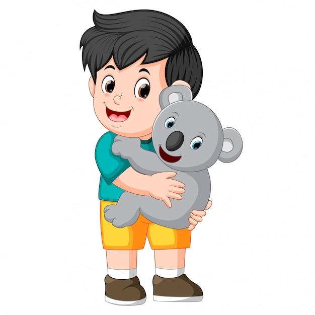 コヤラを抱く少年 Premiumベクター