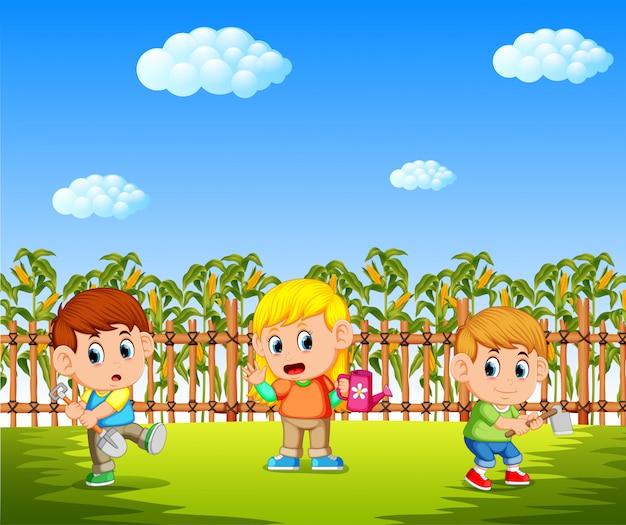 Счастливые дети, посадка на кукурузном поле с использованием садовых инструментов Premium векторы