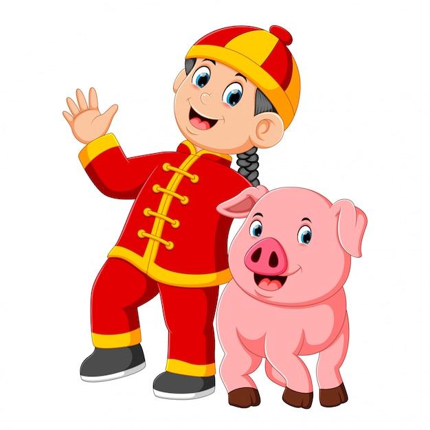 小さな男の子が中国の新年に大きなピンクのブタと遊んでいます。 Premiumベクター