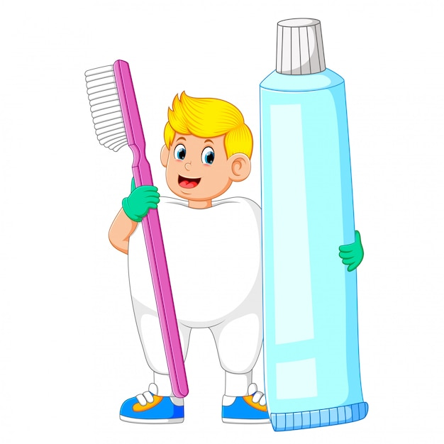 歯の衣装を着て、大きな歯ブラシと大きな歯磨き粉を保持している男 Premiumベクター
