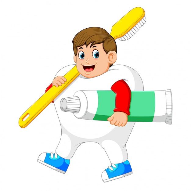 大きな歯ブラシと大きな歯磨き粉を持って歩いて歯のコスチュームを着ている男 Premiumベクター