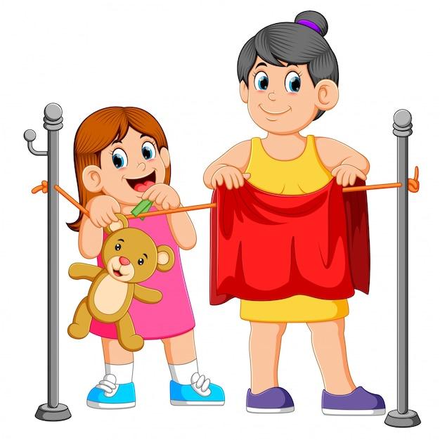 彼女の母親の洗濯物を干すのを助ける少女 Premiumベクター