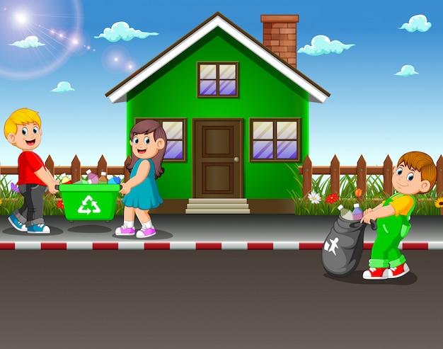 家の通りでゴミを集めるボランティアの子供たち Premiumベクター