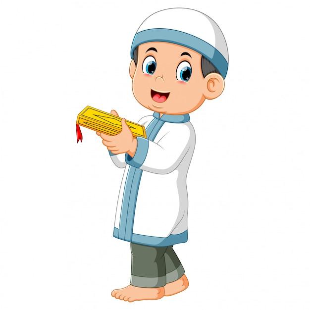 Высокий мальчик стоит и держит аль-коран своими руками Premium векторы